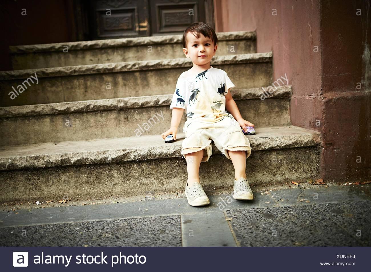 Boy sitting on steps - Stock Image
