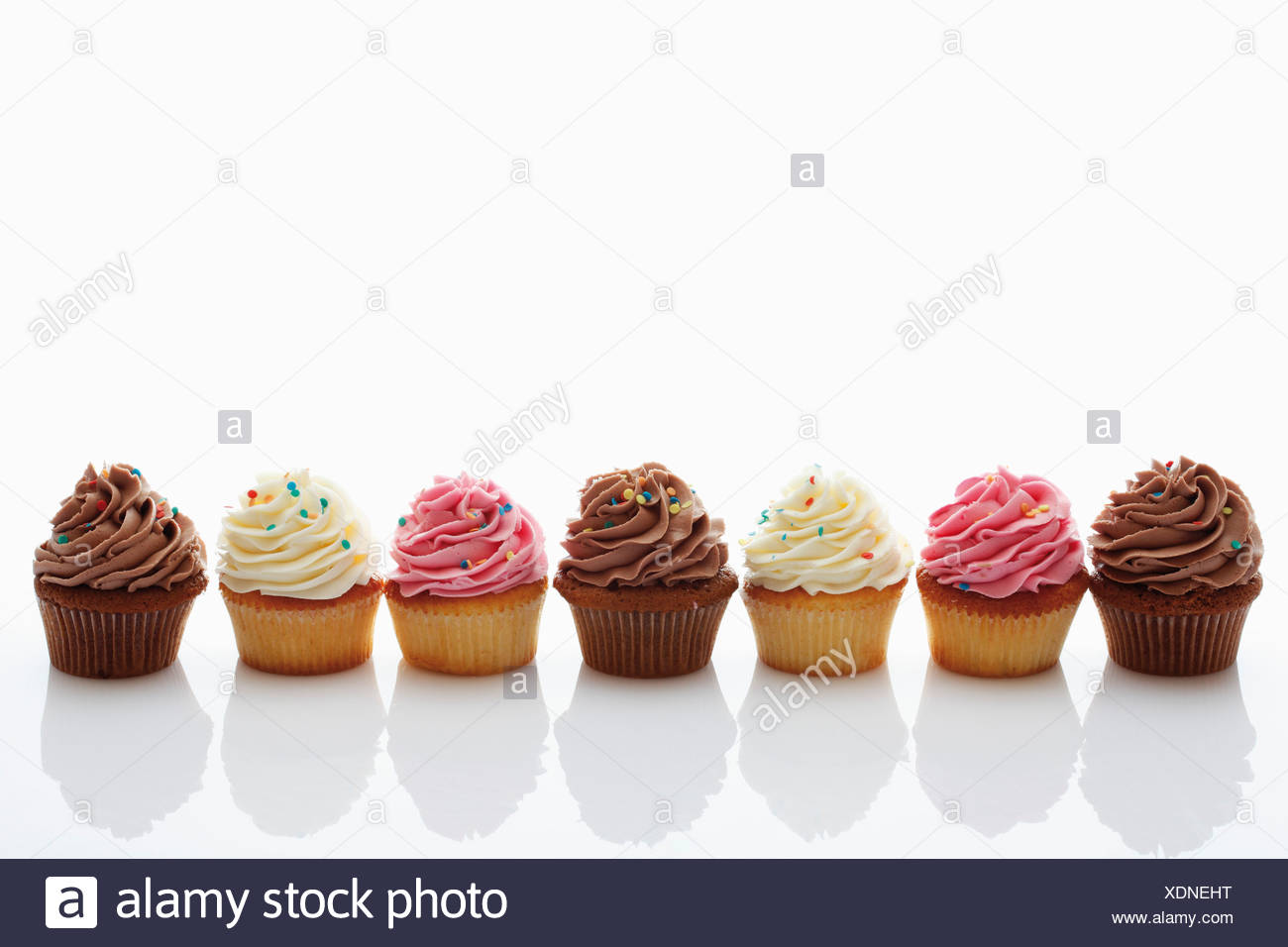 Close up of strawberry, vanilla and chocolate buttercream cupcakes against white background - Stock Image