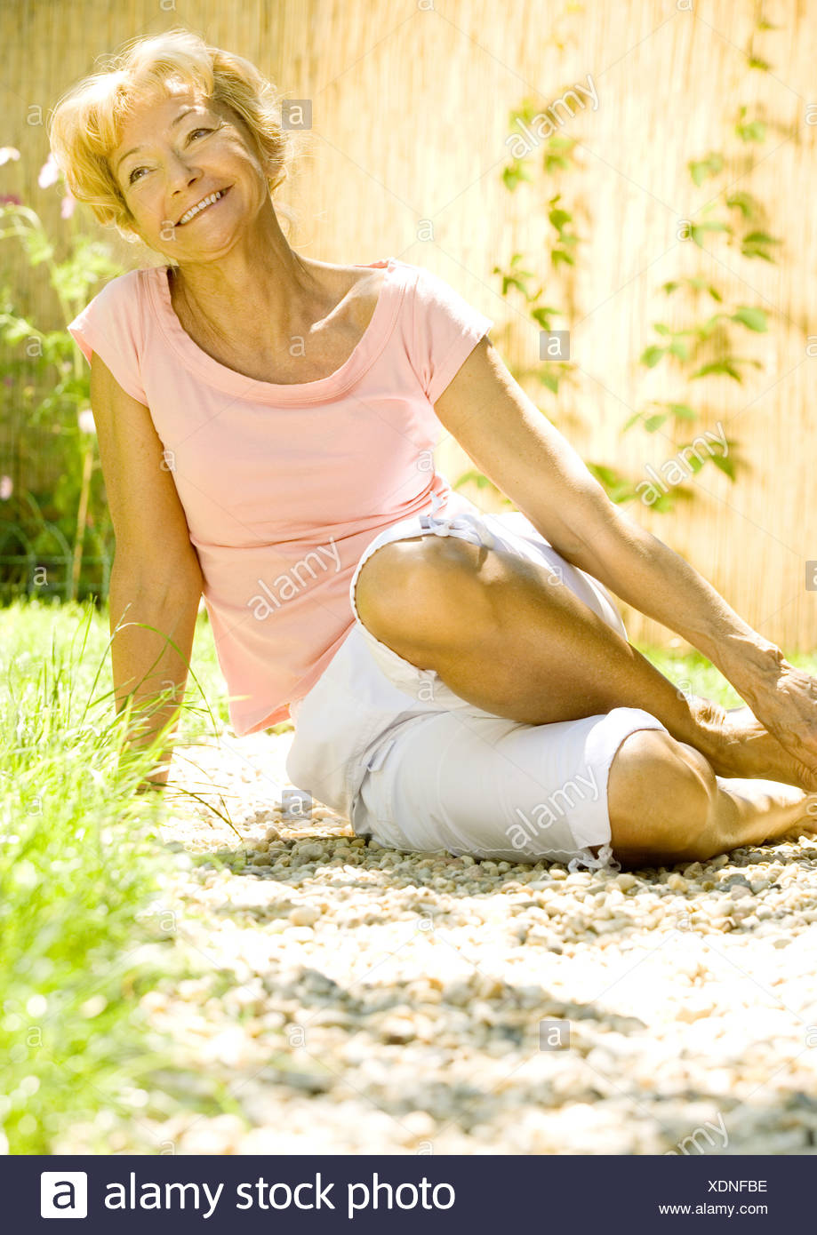 Senior woman sitting on ground outdoors, smiling - Stock Image