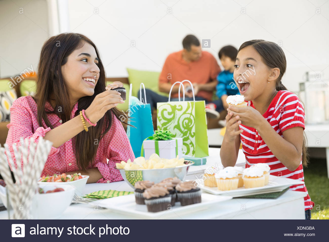 Siblings eating cupcakes at birthday party - Stock Image