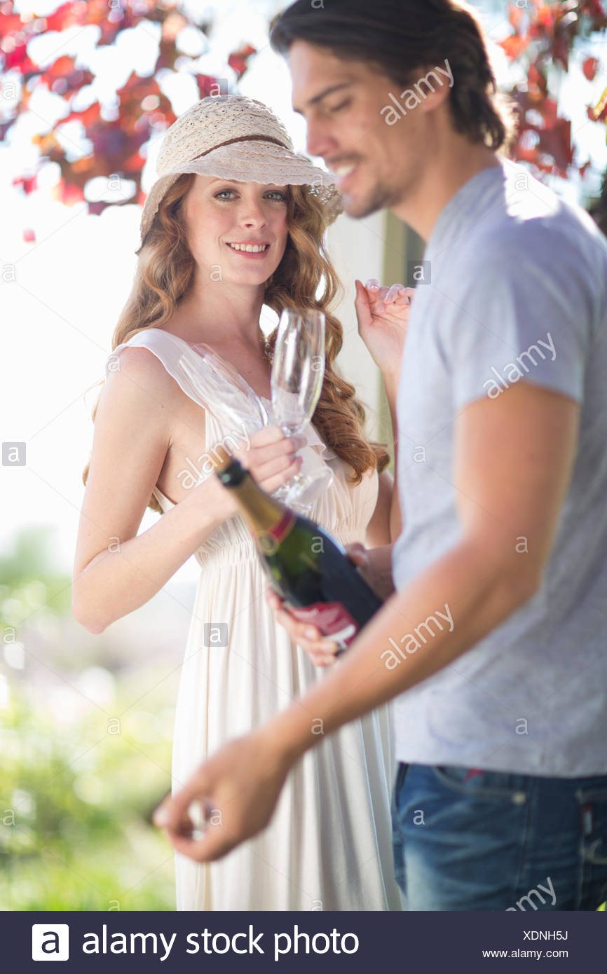 Couple preparing to celebrate with champagne in garden wine bar - Stock Image