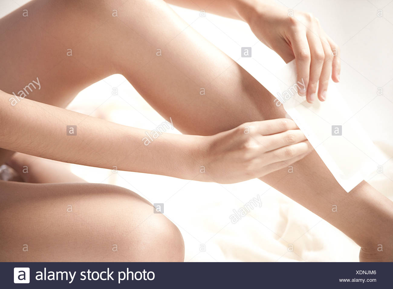 Woman waxing legs, cropped - Stock Image