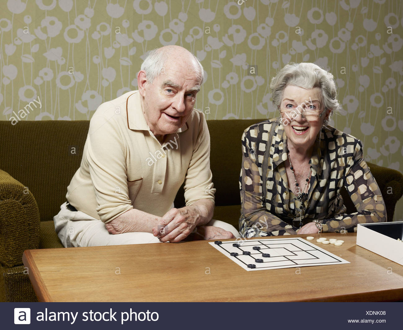 Senior man and woman play muehle on couch - Stock Image