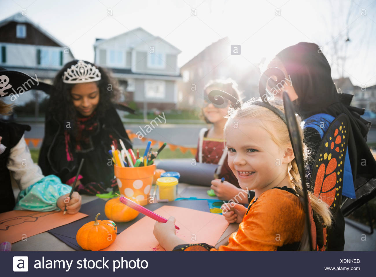 Kids in Halloween costumes doing crafts front yard - Stock Image