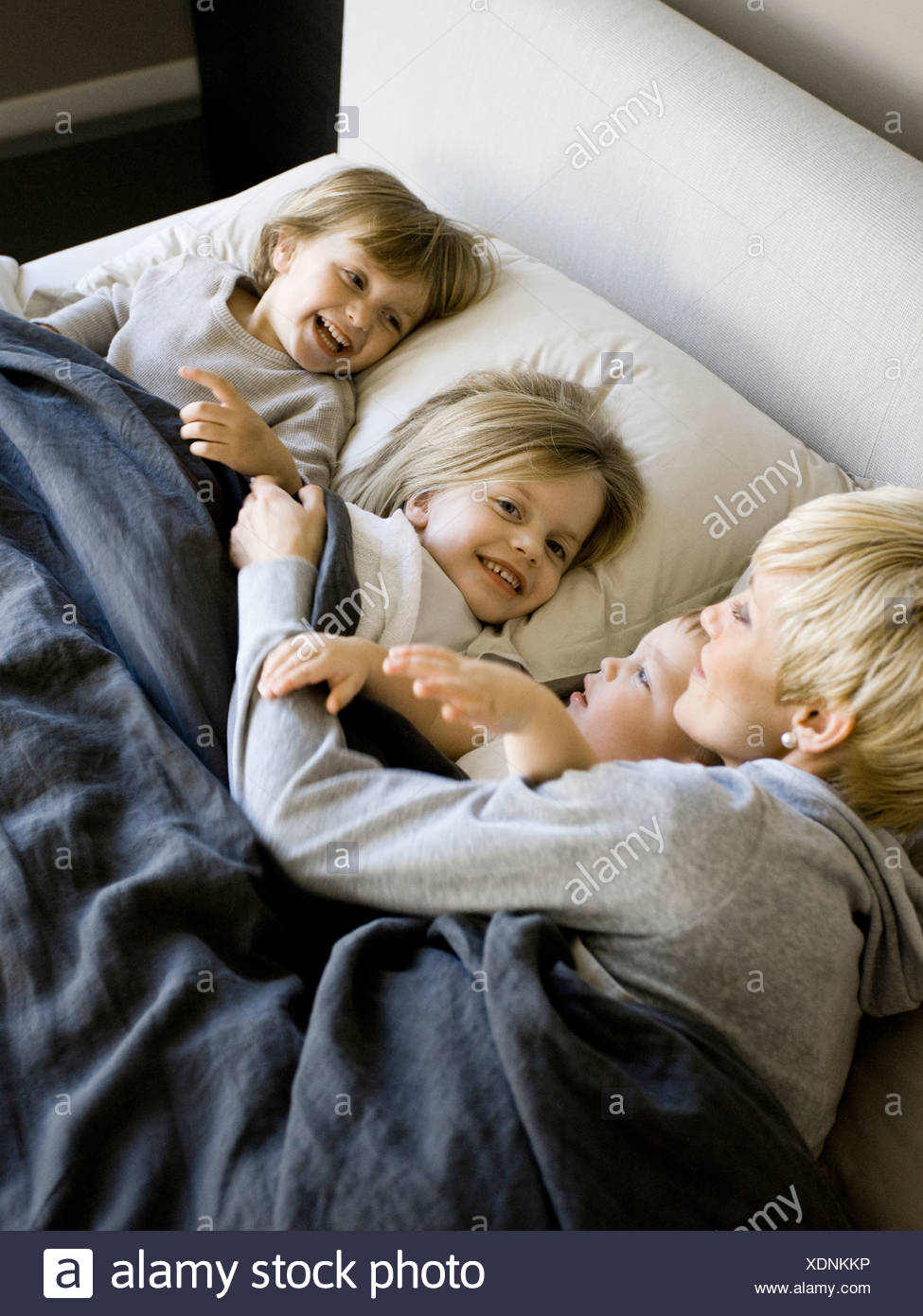 USA, Utah, Provo, Mother in bed with children (18-23 months), (2-5) - Stock Image