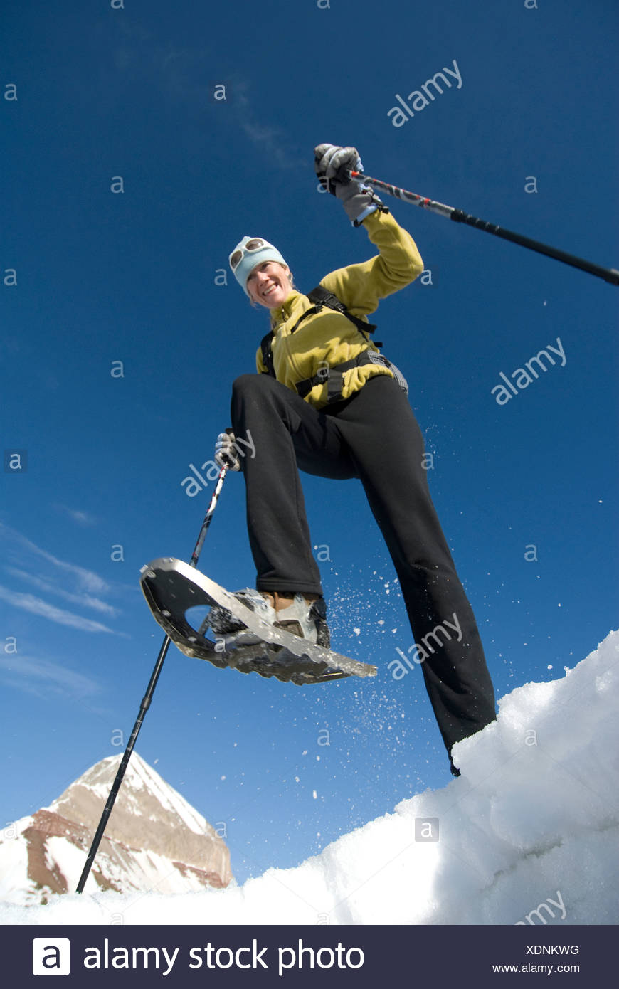 Woman snowshoeing below mountain, San Juan National Forest, Colorado. - Stock Image