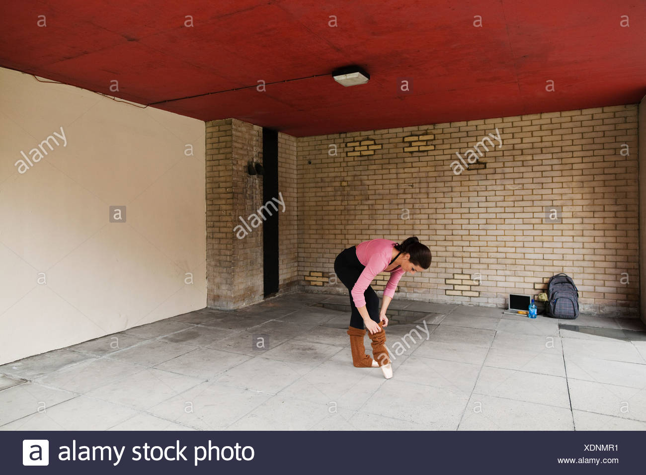 Woman adjusting leg warmers before work out - Stock Image
