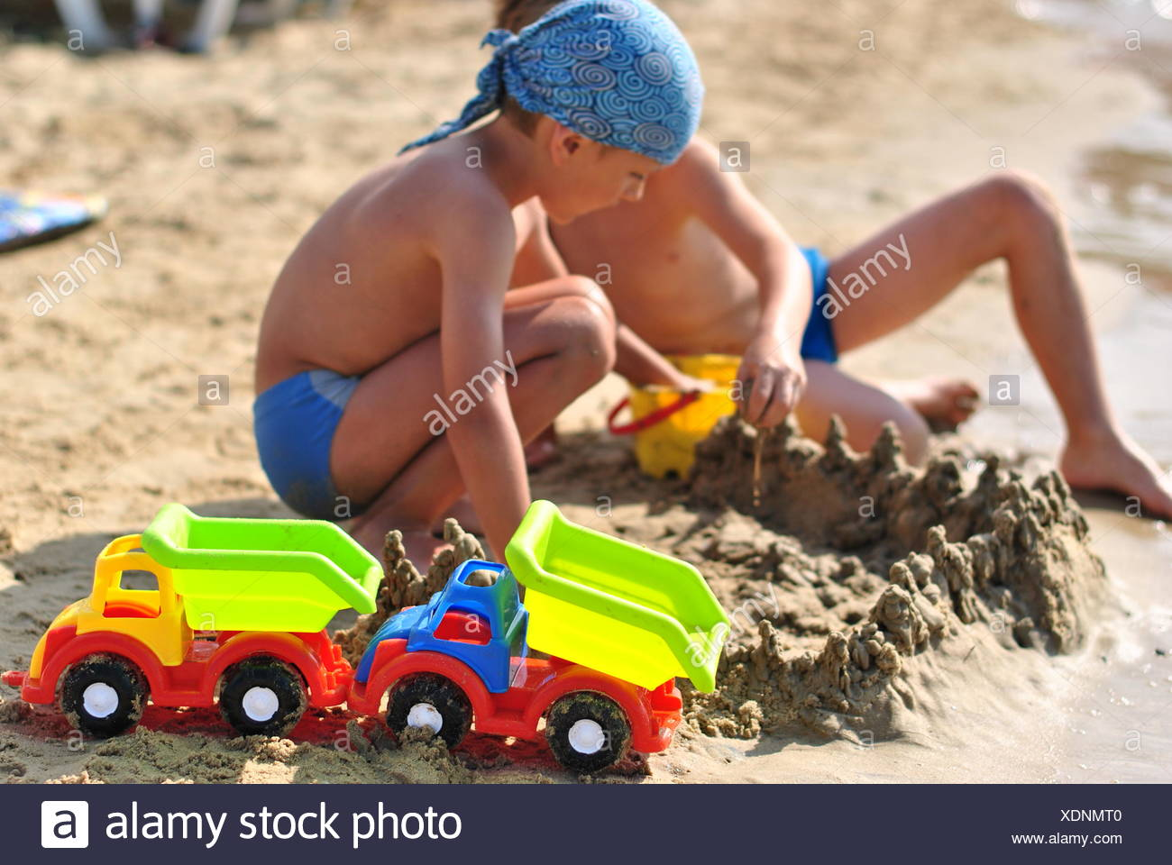 Children (4-5) playing on sandy beach - Stock Image