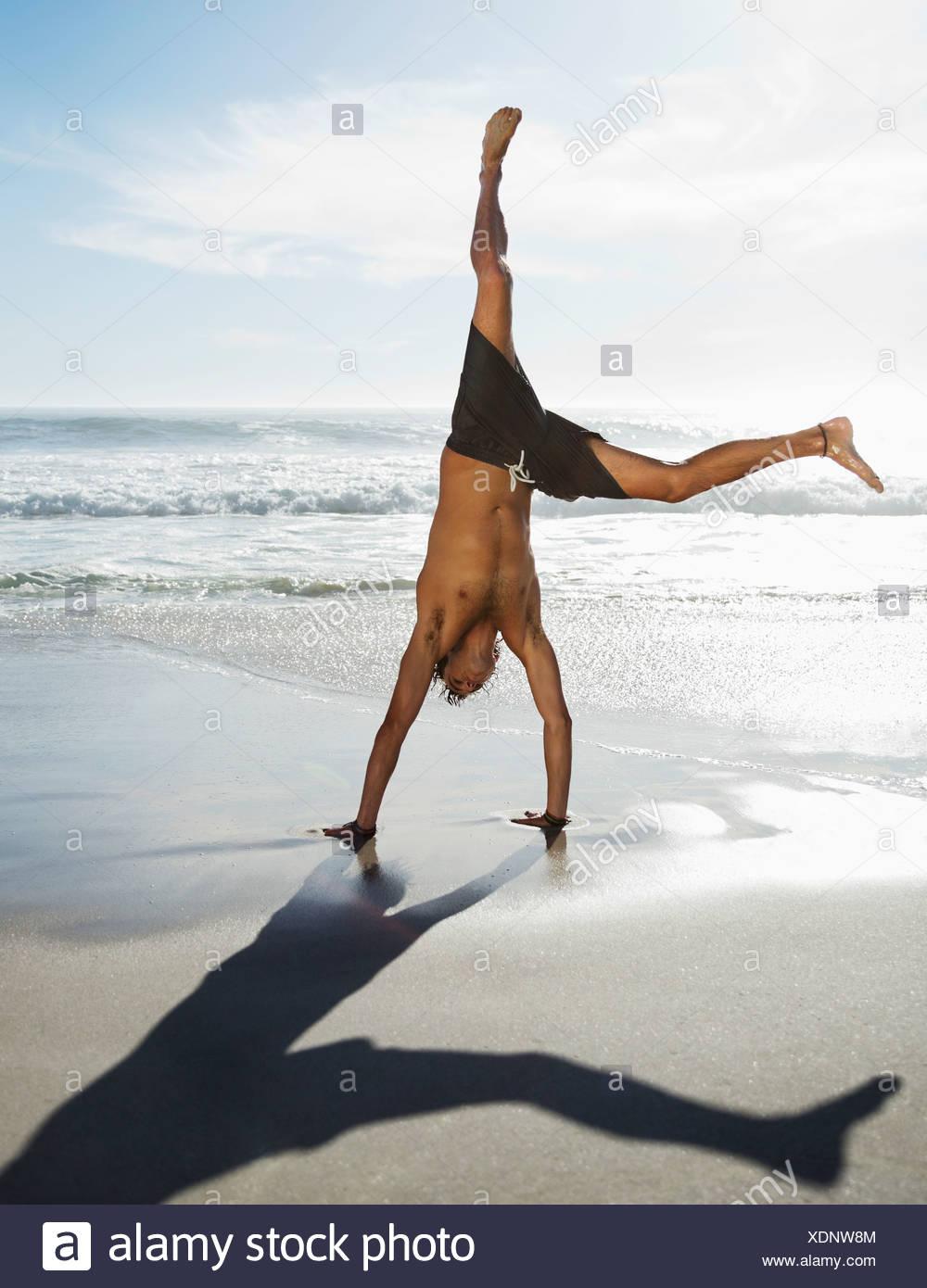 Man in swim trunks doing handstand on beach - Stock Image