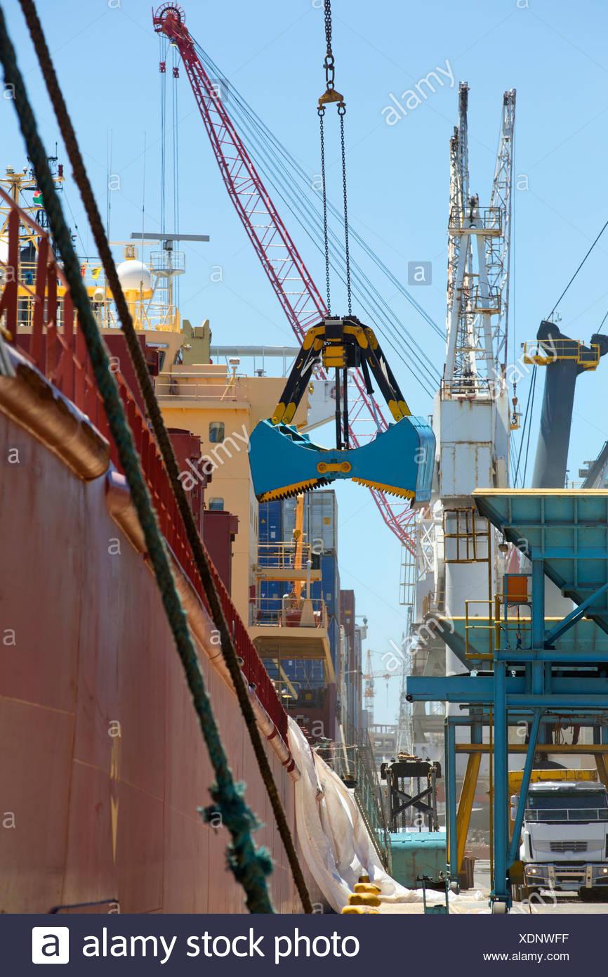 Grab bucket unloading grain from bulk tanker in commercial dock - Stock Image