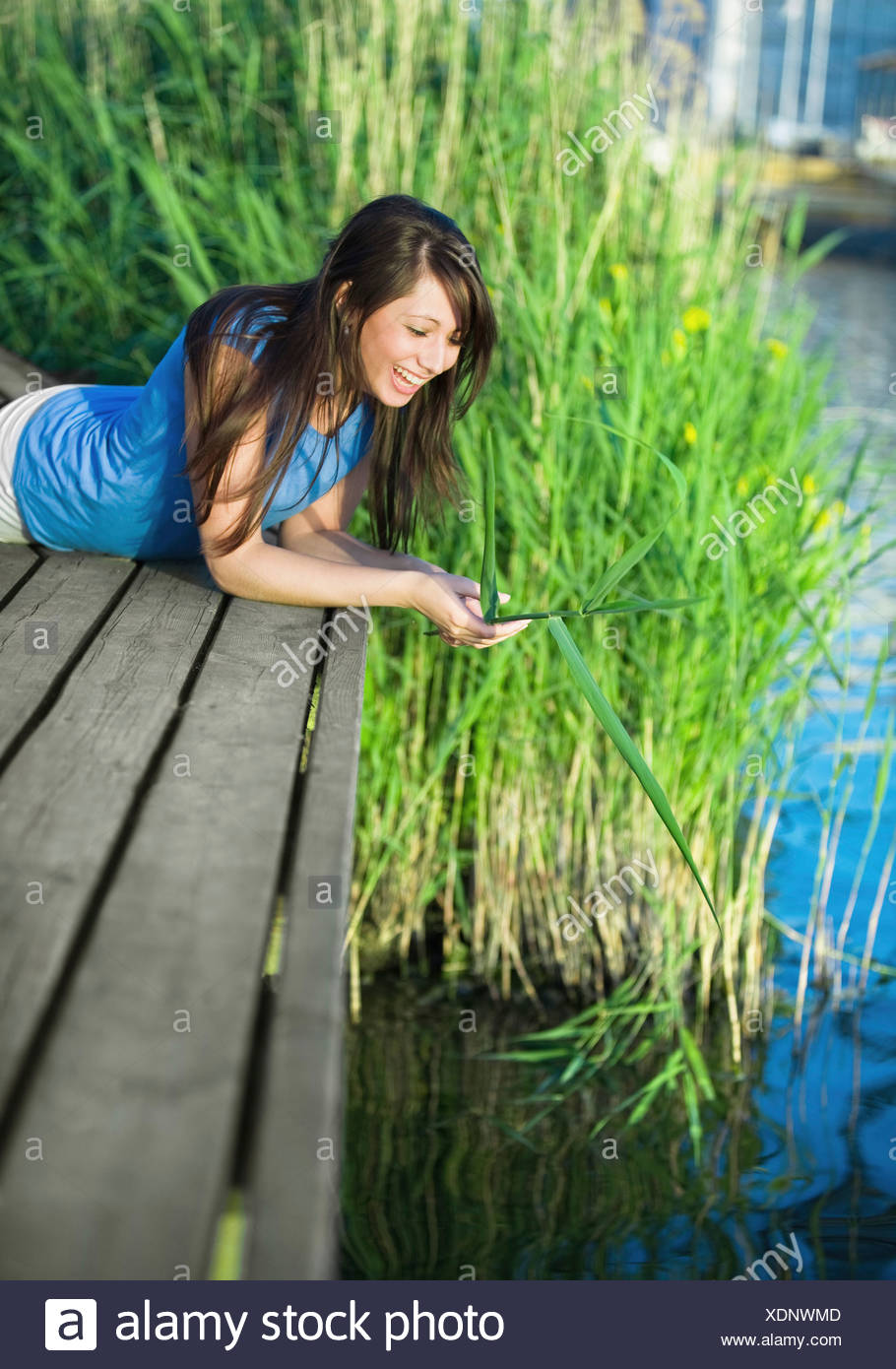 Girl lying on a jetty - Stock Image