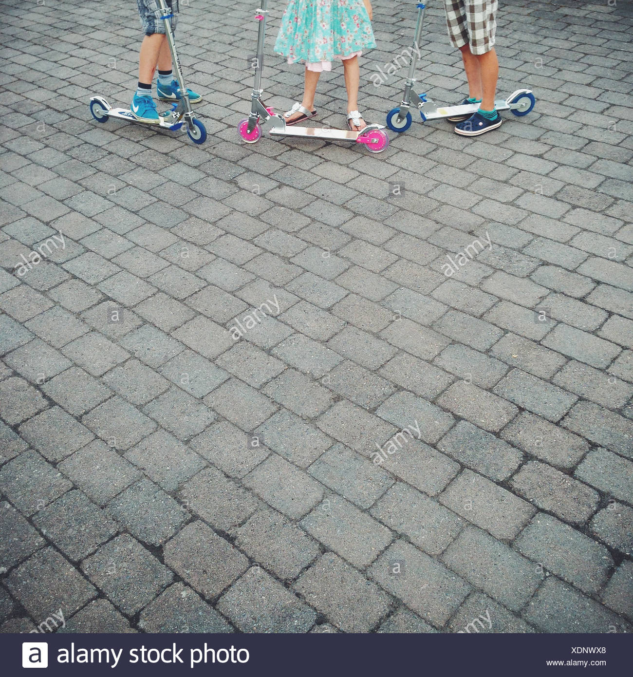 Close up of children (10-11, 12-13) standing next to scooters Stock Photo