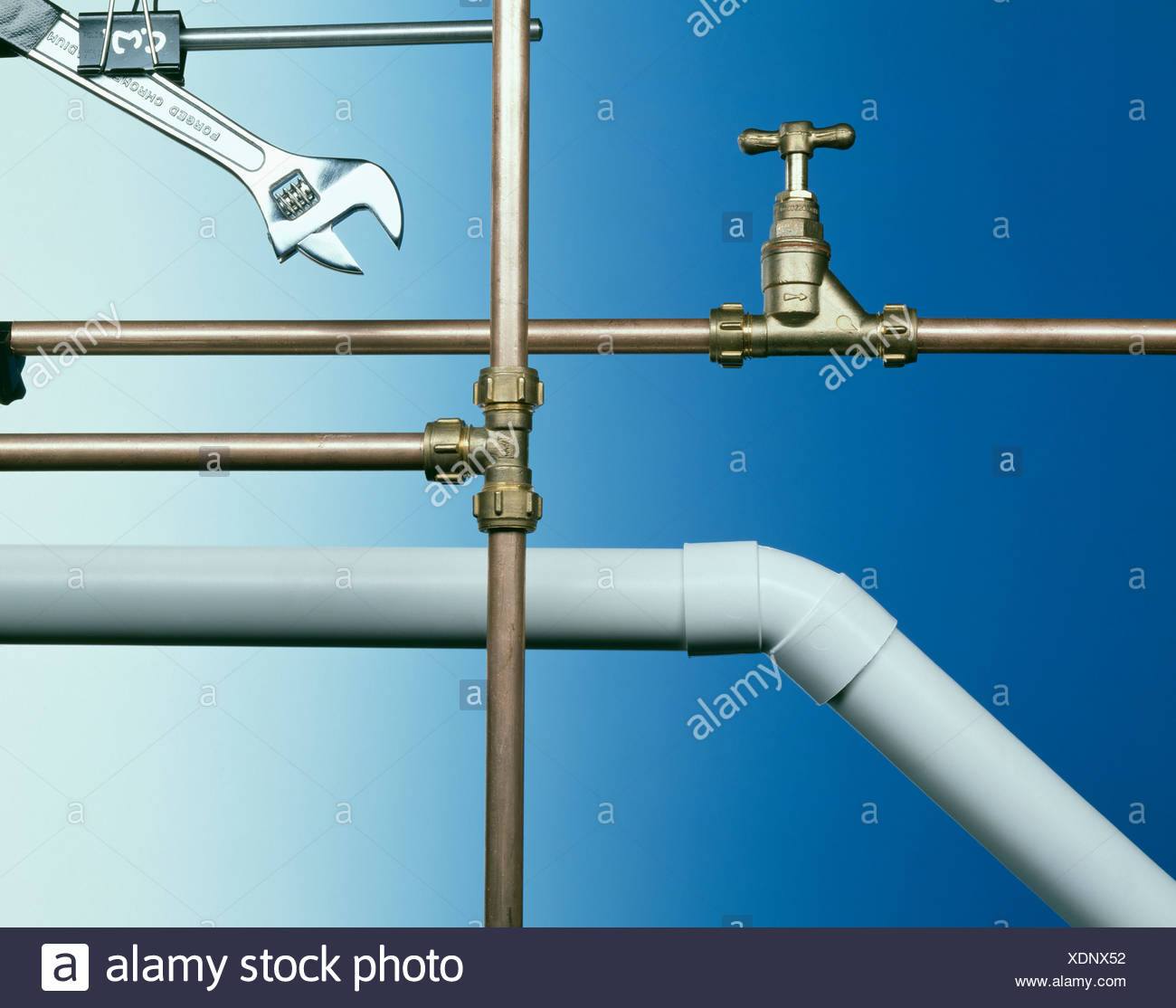 Close Up Of Copper Tap And Plumbing Pipes With Wrench And White