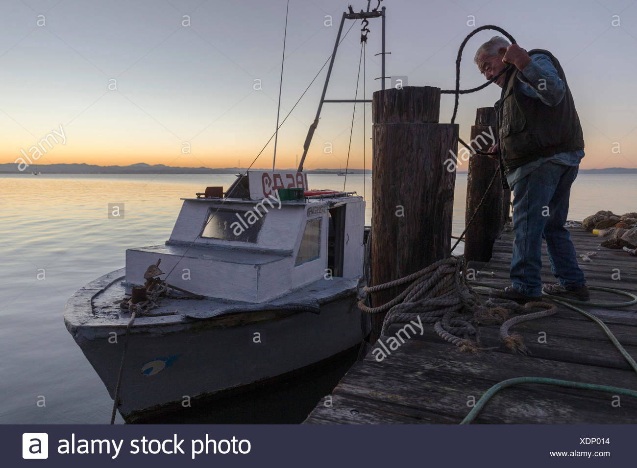 shrimp fisherman standing on pier near boat at sunset,China Camp,California,USA - Stock Image