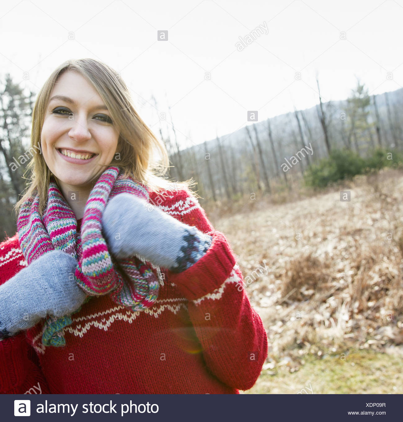 A woman wearing a knitted scarf and woollen mittens outdoors on a winter day. - Stock Image