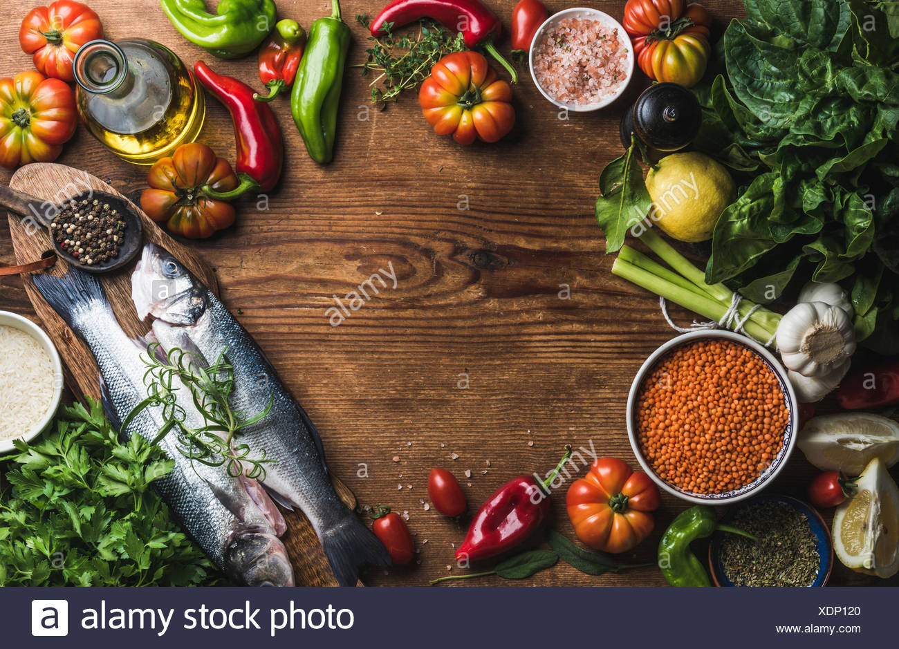 Ingredients for cooking healthy dinner. Raw uncooked seabass fish with vegetables, grains, herbs and spices over rustic wooden b - Stock Image