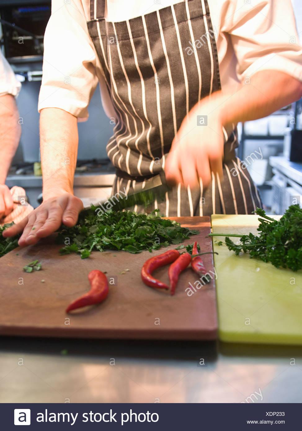 Chef chopping in restaurant kitchen - Stock Image