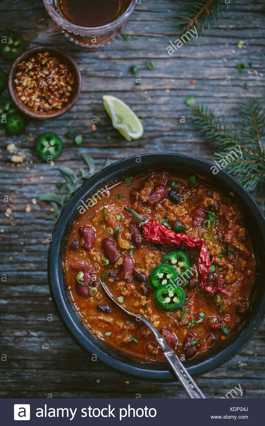 A bowl of turkey and bean chili topped off with slices of jalapeno and a hot dried serrano pepper is photographed from the top v - Stock Image