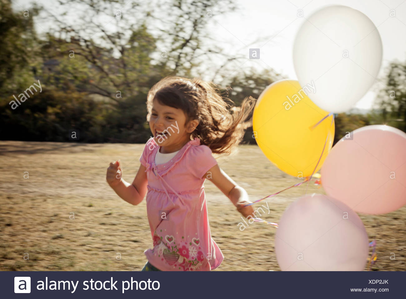 Girl running with balloons - Stock Image