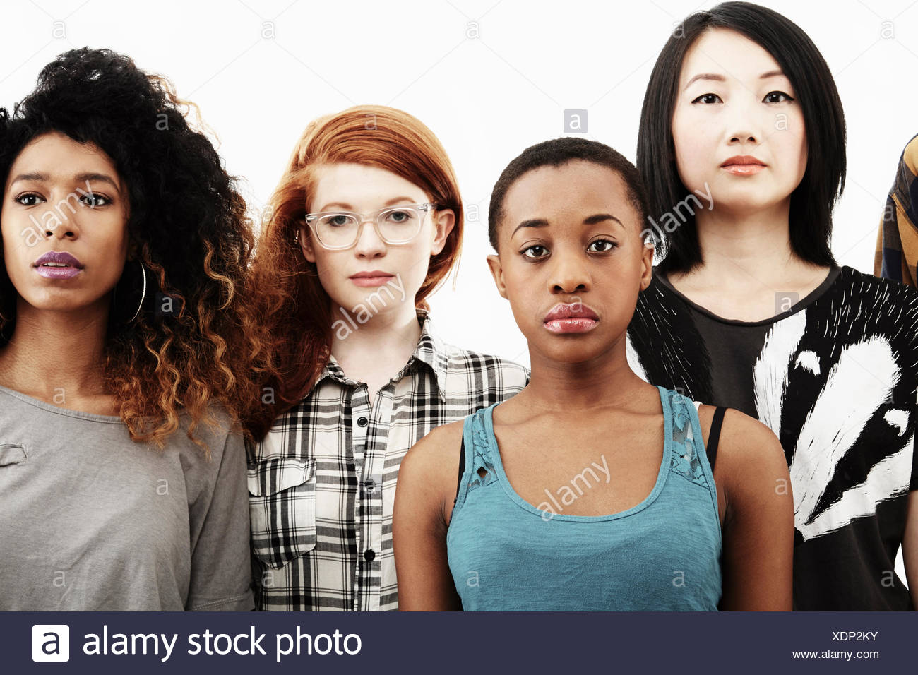 Formal studio portrait of four young women with blank expressions - Stock Image