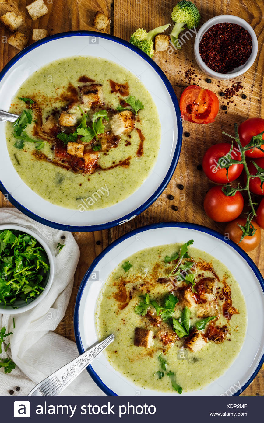 Cream of broccoli soup in two white bowls with spoons, garnished with a chili powder sauce, croutons and parsley. Accompanied by extra chopped parsley - Stock Image