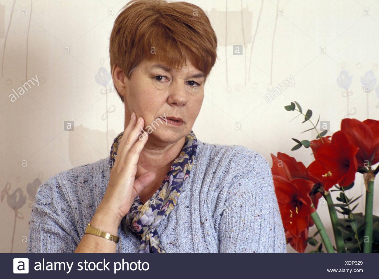 Furrowing brow senior woman looking moody at the camera - Stock Image