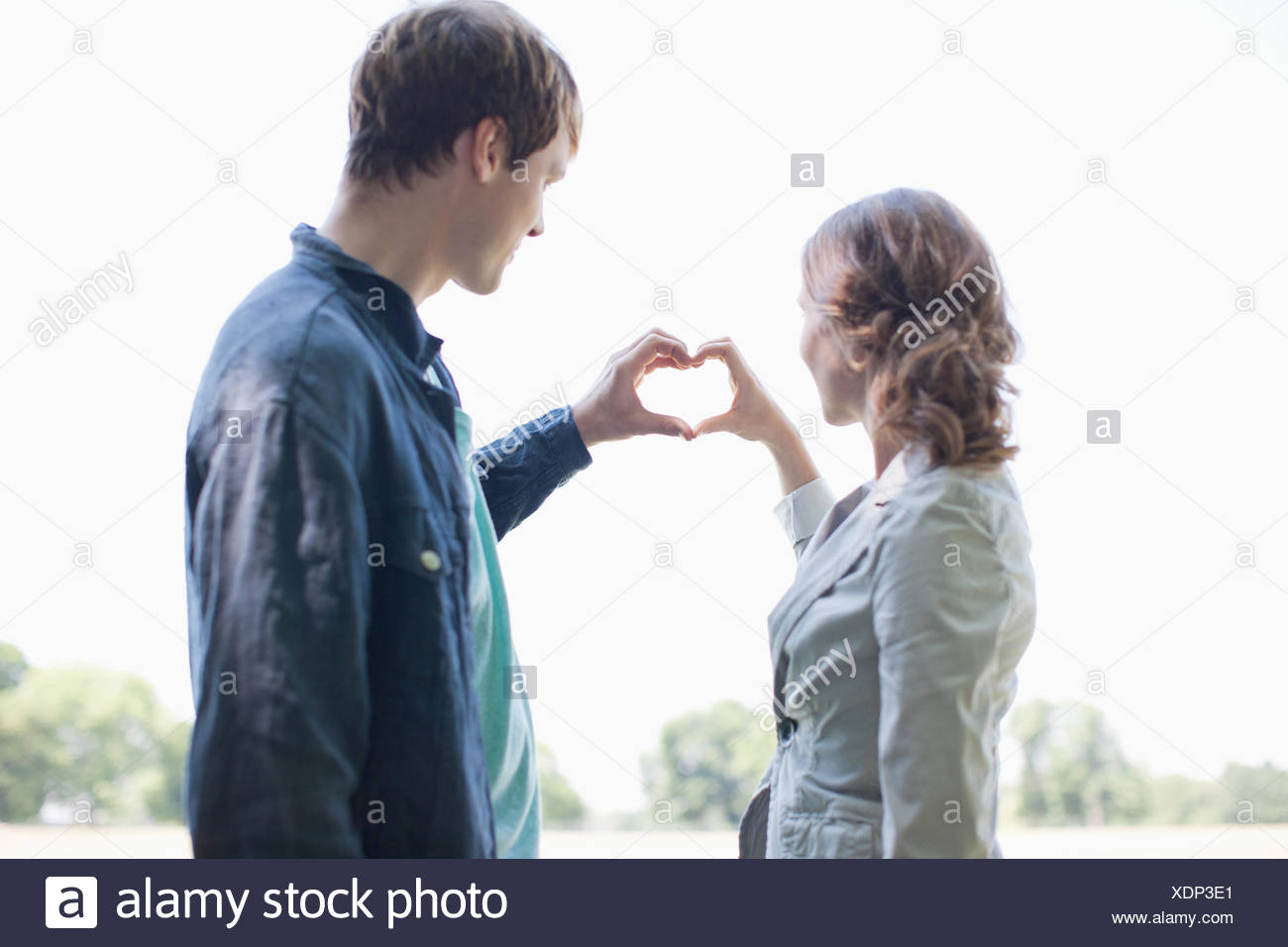 Smiling couple using hands to make heart shape Stock Photo