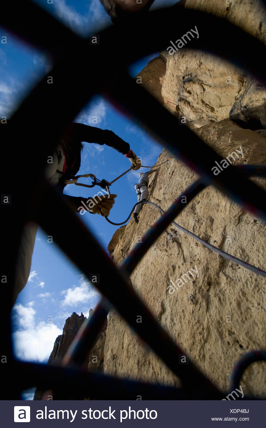 Peering up through a climbing rope at a belayer giving slack to a climber. - Stock Image