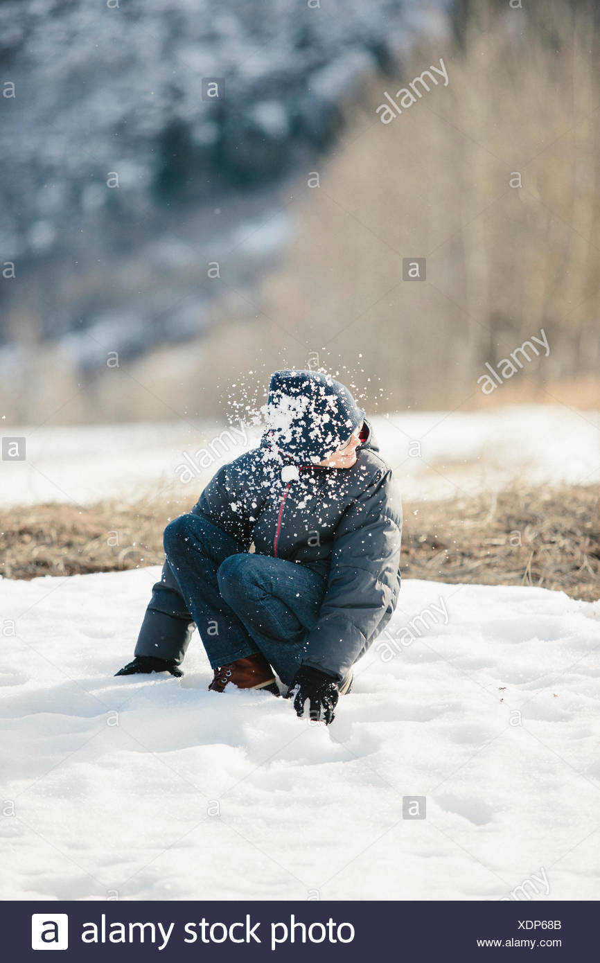 A boy in a blue coat and woolly hat turning his head from a snowball which has hit him. - Stock Image