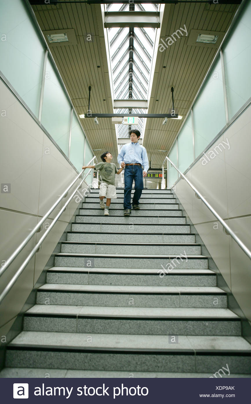 Low angle view of a young man and his son walking down stairs Stock Photo