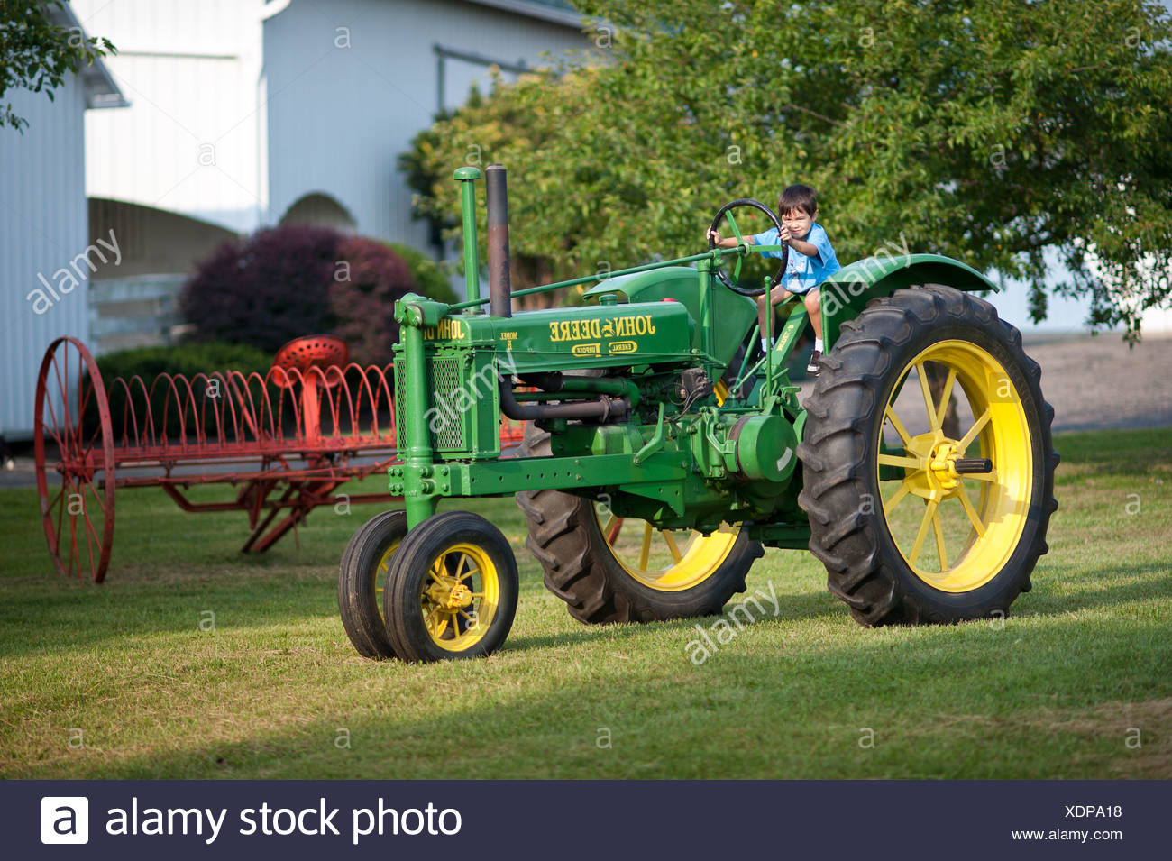 Young boy rides a restored antique John Deere Model B tractor. - Stock Image