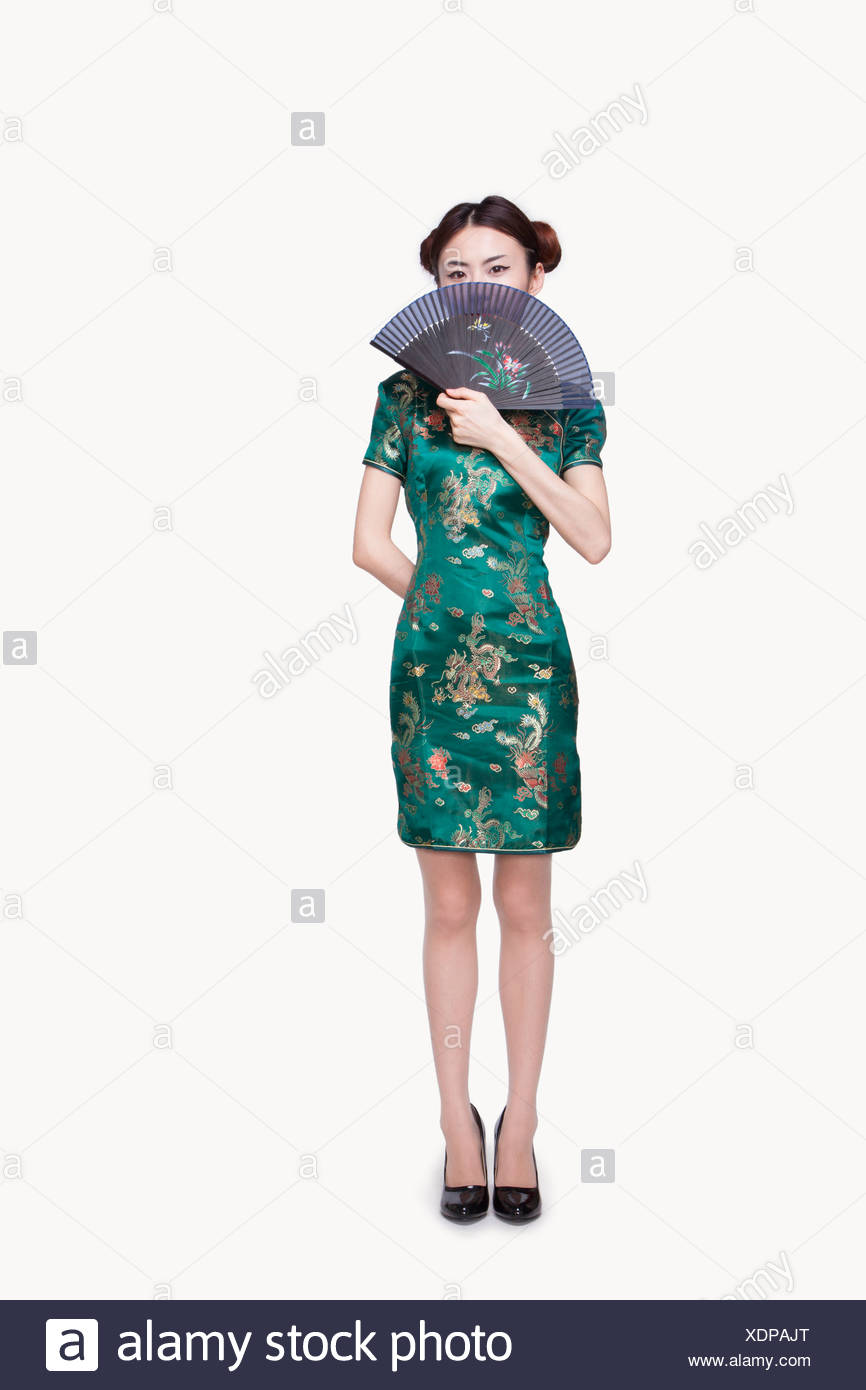 Young Woman with Qipao Covering Her Face with Fan - Stock Image