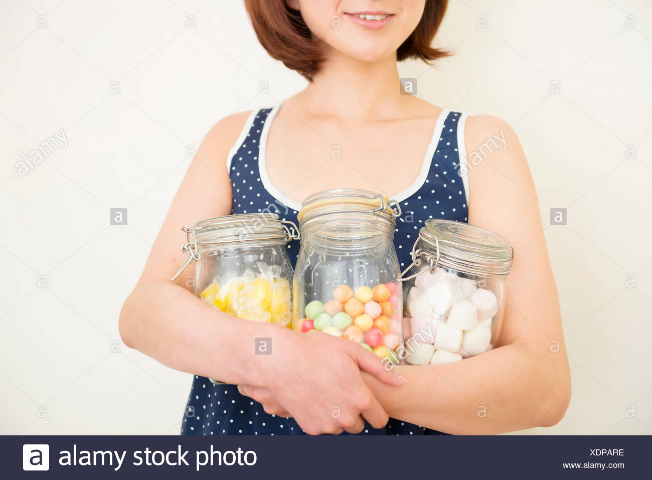 Woman hugging three jars of marshmallows, bubble gum and sherbet lemons - Stock Image