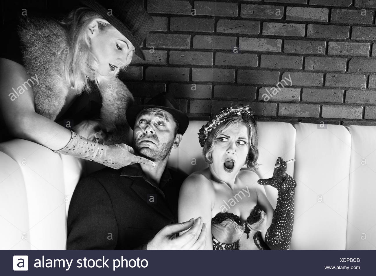 Caucasian prime adult male torn between two Caucasian prime adult females - Stock Image