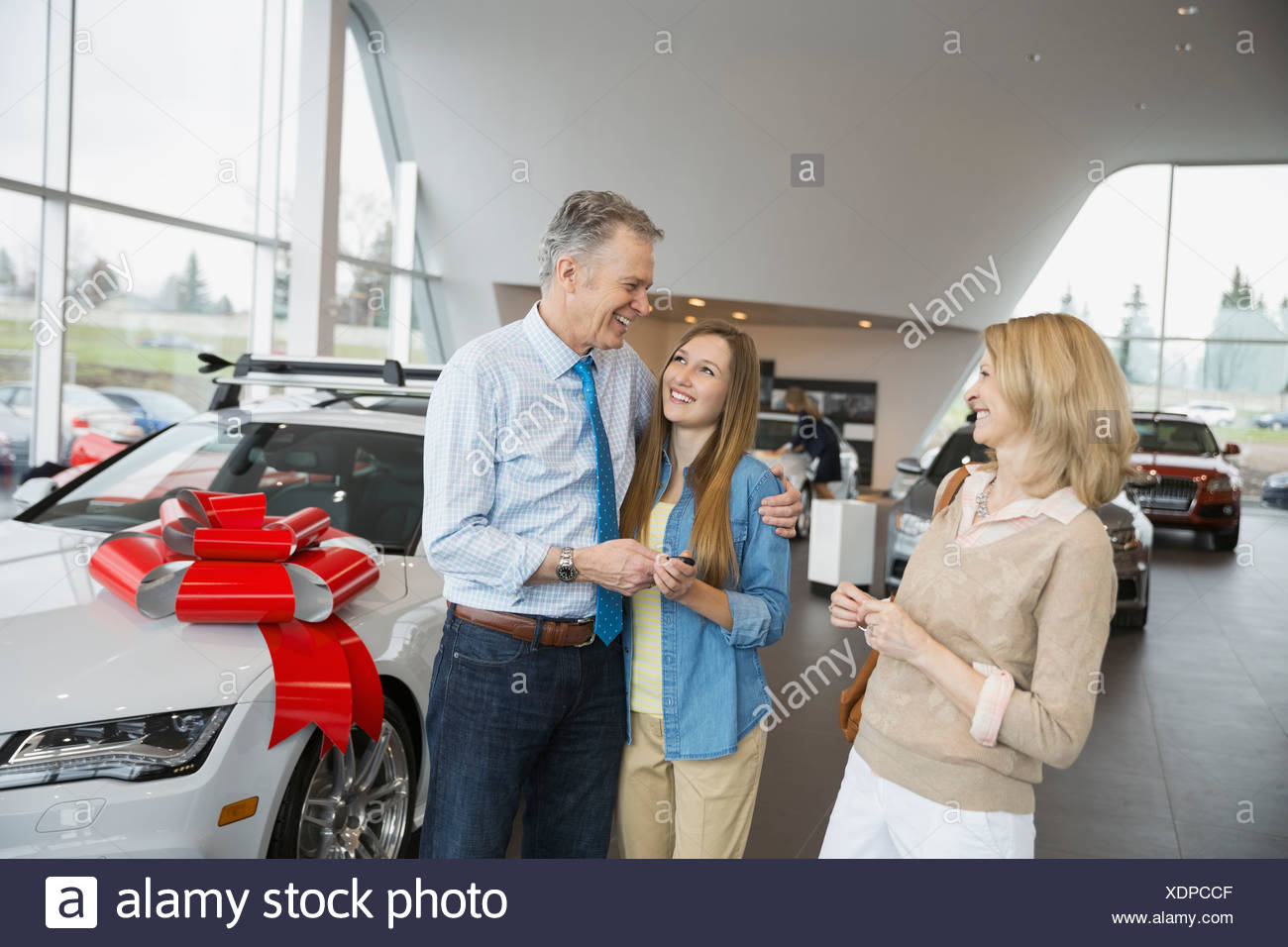 Parents buying daughter car in dealership showroom - Stock Image
