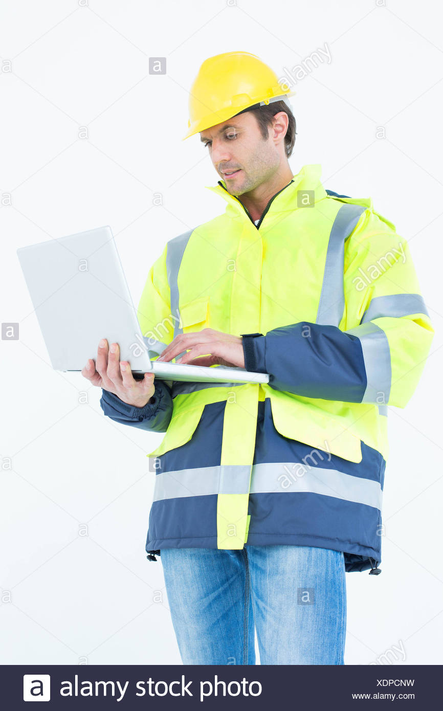 Architect in reflective clothing using laptop computer - Stock Image