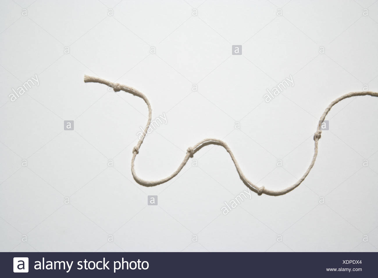 Knotted string in a curved shape - Stock Image
