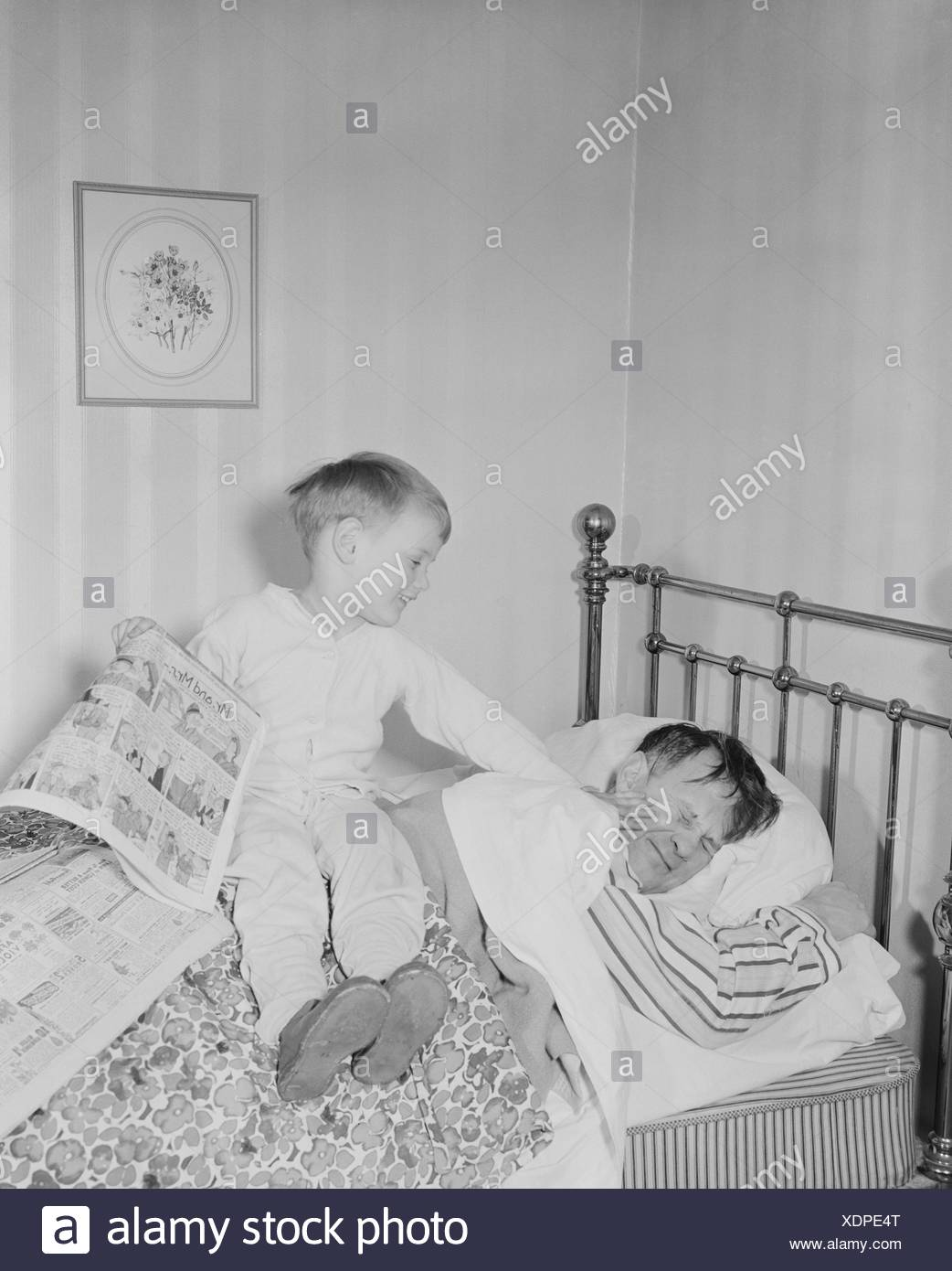 Boy waking father in bedroom - Stock Image