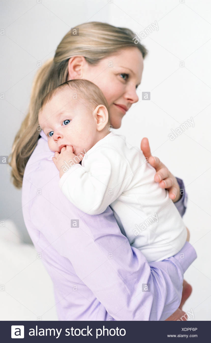 Mother and baby. Mother holding her baby daughter who is sucking her thumb. - Stock Image