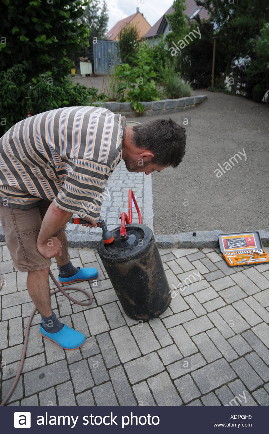 Laying sod, fill roller with water - Stock Image