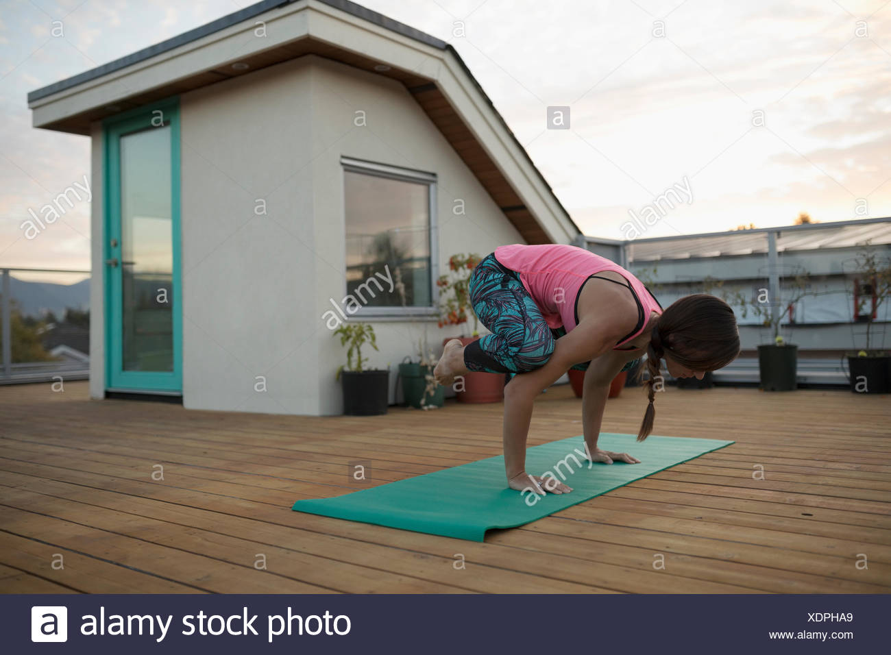 Woman practicing yoga crow pose on yoga mat on patio deck - Stock Image