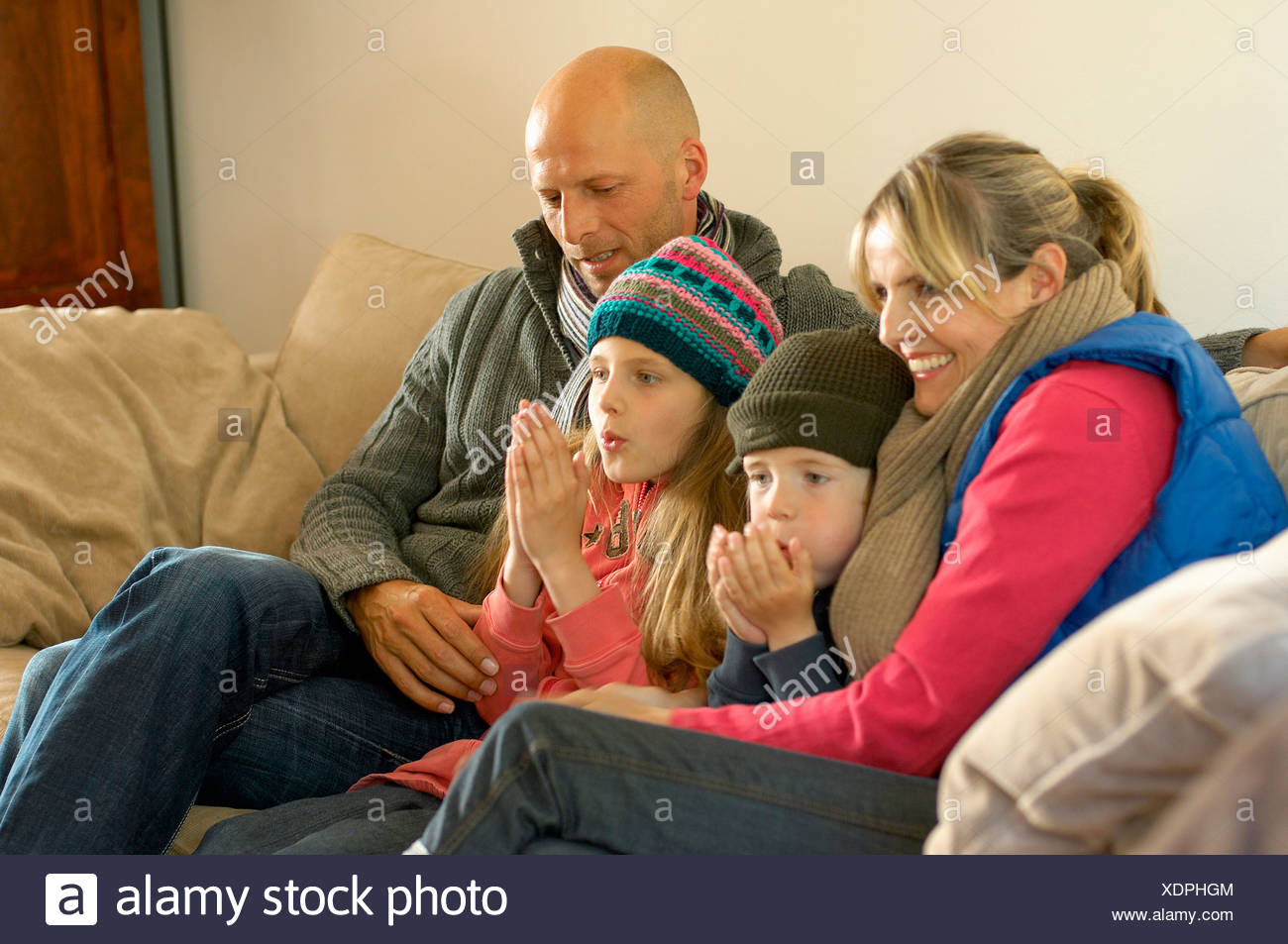 Family winter clothes keeping warm together on sofa - Stock Image