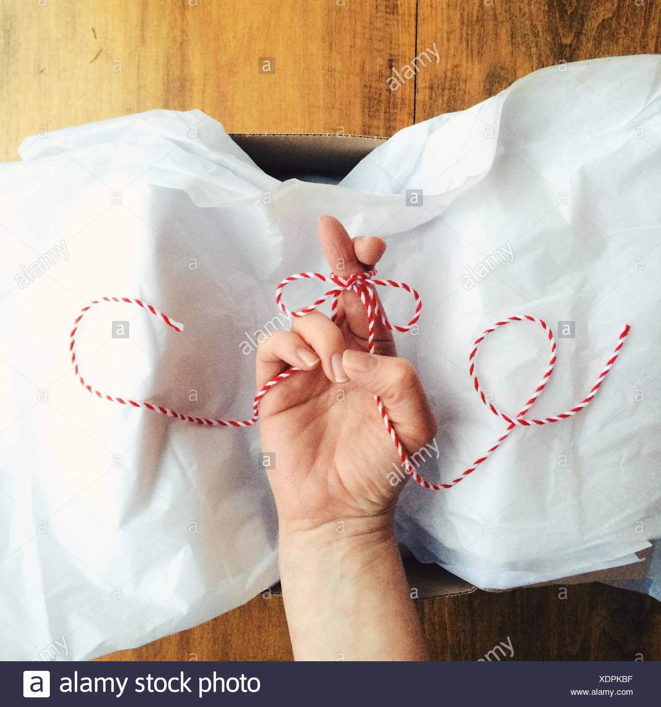 Fingers crossed and tied in a wrapped bow in a box - Stock Image