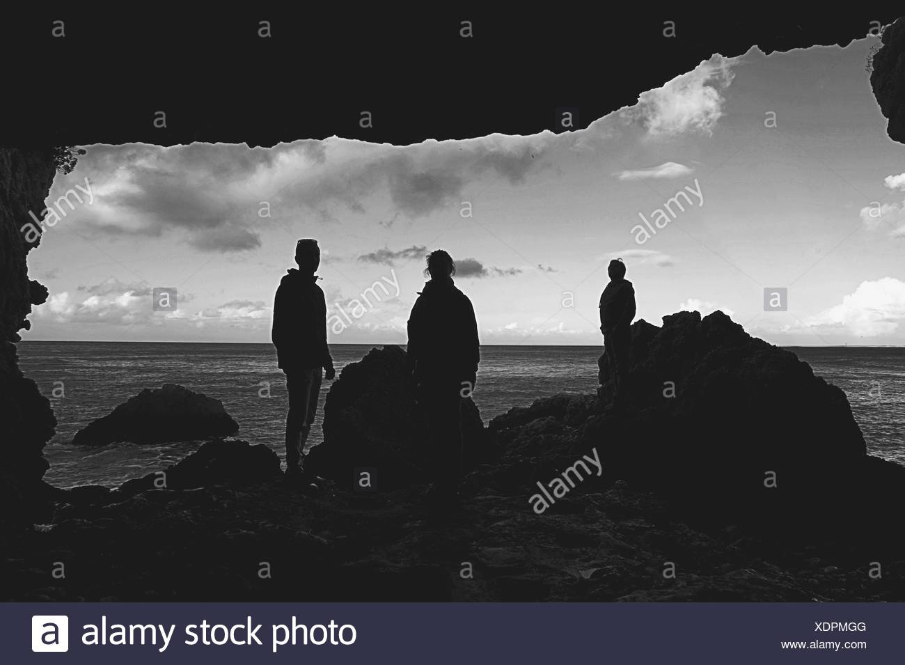 Silhouette People Standing At Beach By Rocks - Stock Image
