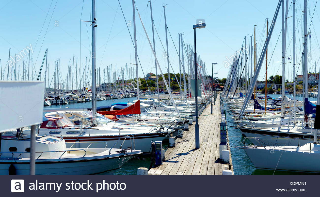Sailboats anchored at the harbor against clear blue sky - Stock Image