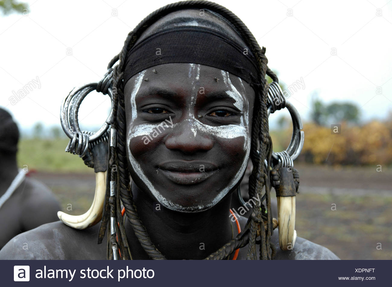 Portrait of a smiling young man from the Mursi tribe, wild, heavy headdress made of teeth of a male boar, near Jinka, Ethiopia, - Stock Image