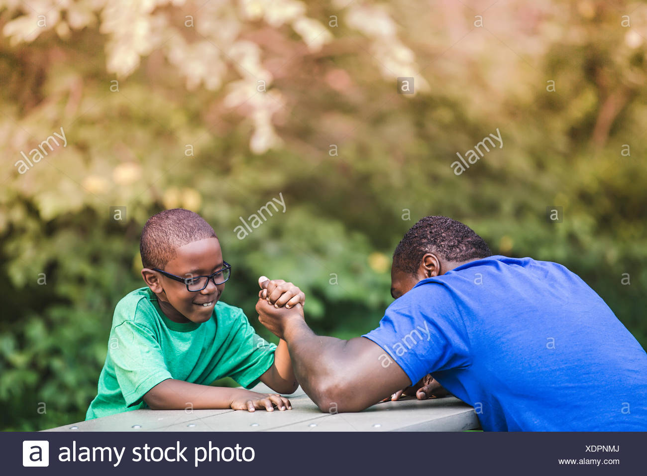 Father arm wrestling with son at parkland eco camp - Stock Image