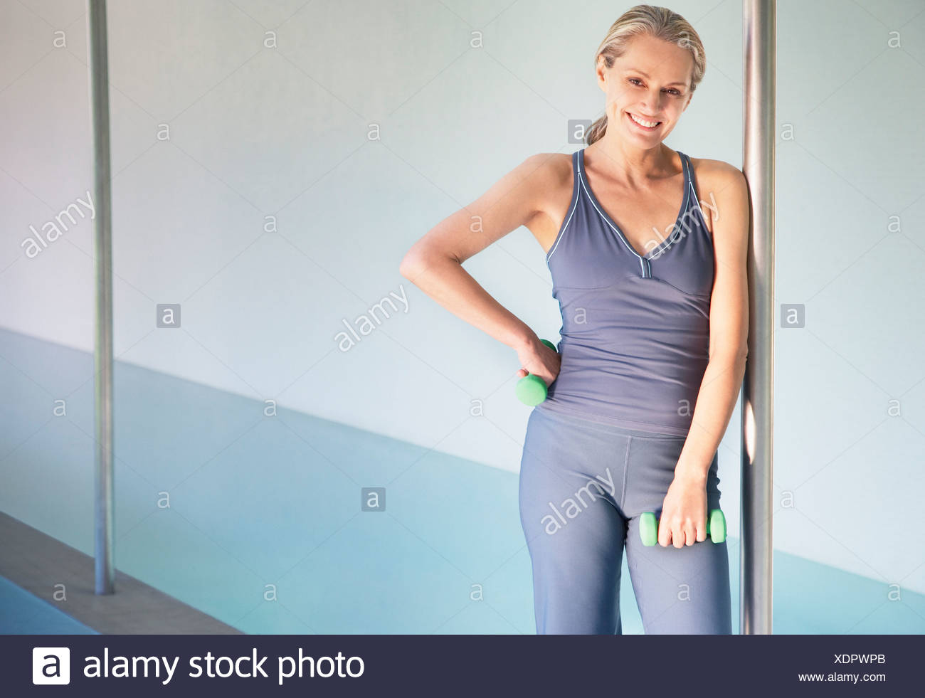 Woman holding small free weights by an indoor pool - Stock Image