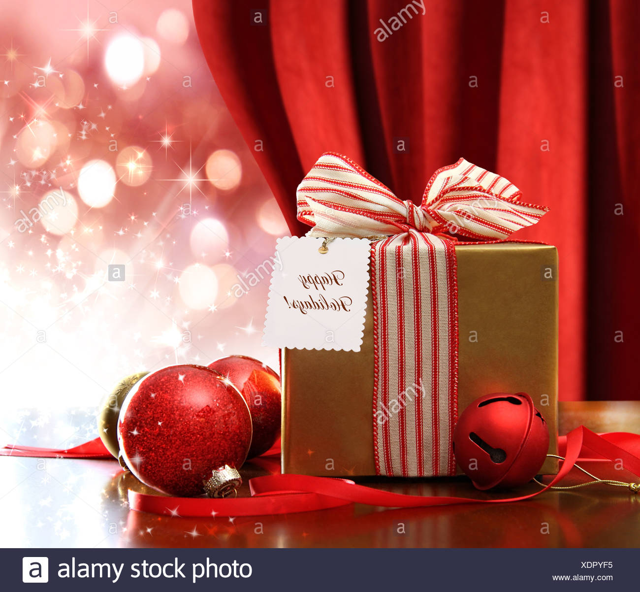 Gold Christmas gift box and ornaments with sparkle lights in background - Stock Image