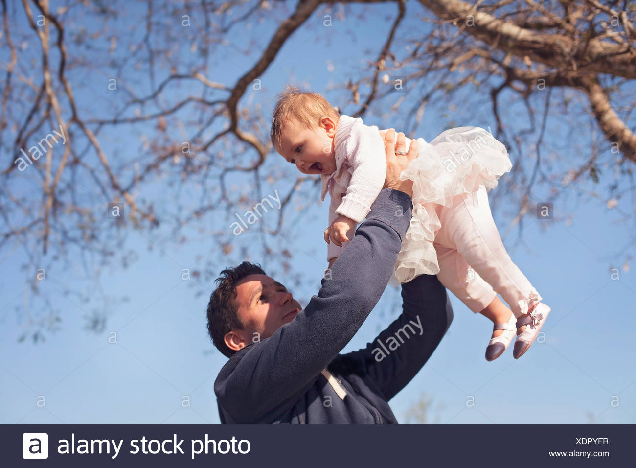 Father holding aloft smiling daughter (6-11 months) - Stock Image